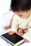 Jeu asiatique de jeu de bébé avec la tablette Photo libre de droits