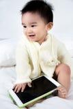 Jeu asiatique de jeu de bébé avec la tablette Photo stock