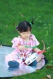 Jeu chinois insouciant de bébé sur la pelouse Image libre de droits