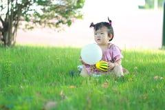 Jeu chinois insouciant de bébé une boule et un ballon sur la pelouse Photos stock