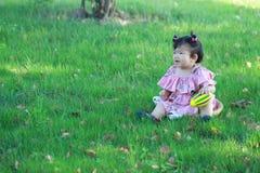 Jeu chinois insouciant de bébé une boule sur la pelouse Photographie stock