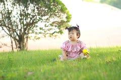 Jeu chinois insouciant de bébé une boule sur la pelouse Images libres de droits