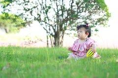 Jeu chinois insouciant de bébé une boule sur la pelouse Image libre de droits