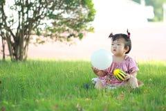 Jeu chinois insouciant de bébé une boule sur la pelouse Photographie stock libre de droits