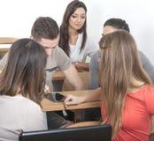 Jeu d'étudiants avec le PC de comprimé dans la salle de classe Photos stock