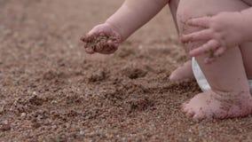 Jeu d'enfant avec le sable dans le mouvement lent sur la plage banque de vidéos