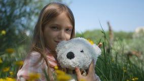 Jeu d'enfant extérieur en parc, sourire heureux, fille ondulant au revoir en nature photos stock