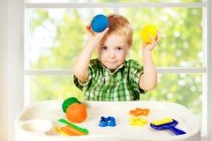 Jeu d'enfant modelant la pâte à modeler, l'enfant et le Clay Dough coloré, jouets Photographie stock