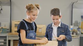Jeu d'enfants à l'atelier de métier Petit garçon mignon et sa soeur école-âgée jouant avec les morceaux demi-complets en bois banque de vidéos