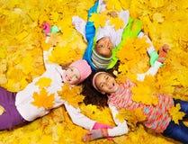Jeu d'enfants avec des feuilles d'orange d'érable d'automne Photographie stock