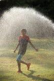 Jeu d'enfants avec des jets de l'eau Photo stock
