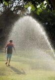 Jeu d'enfants avec des jets de l'eau Images libres de droits