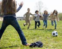 Jeu d'enfants avec la boule dehors au printemps Photos libres de droits