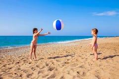 Jeu d'enfants avec la boule sur la plage Images libres de droits
