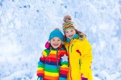 Jeu d'enfants avec la neige en parc d'hiver Photo stock