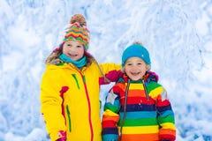 Jeu d'enfants avec la neige en parc d'hiver Images stock