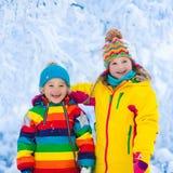 Jeu d'enfants avec la neige en parc d'hiver Image stock