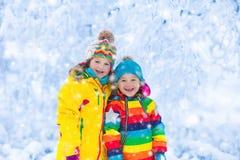 Jeu d'enfants avec la neige en parc d'hiver Image libre de droits