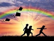 Jeu d'enfants avec le cerf-volant au coucher du soleil Images stock