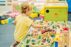 Jeu d'enfants avec le jouet, le chemin de fer de jouet de construction à la maison ou la garde en bois Jeu de garçon d'enfant en  images stock