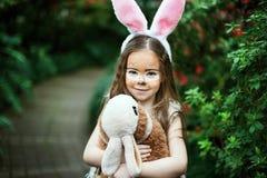 Jeu d'enfants avec le lapin de jouet L'enfant riant à l'oeuf de pâques chassent avec le lapin d'animal familier Petite fille d'en Images libres de droits