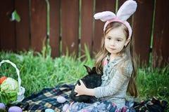 Jeu d'enfants avec le vrai lapin L'enfant riant à l'oeuf de pâques chassent avec le lapin blanc d'animal familier Petite fille d' Photo stock