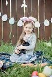 Jeu d'enfants avec le vrai lapin L'enfant riant à l'oeuf de pâques chassent avec le lapin blanc d'animal familier Petite fille d' Image stock