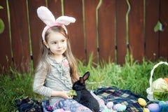 Jeu d'enfants avec le vrai lapin L'enfant riant à l'oeuf de pâques chassent avec le lapin blanc d'animal familier Petite fille d' Images stock