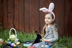 Jeu d'enfants avec le vrai lapin L'enfant riant à l'oeuf de pâques chassent avec le lapin blanc d'animal familier Petite fille d' Photos libres de droits