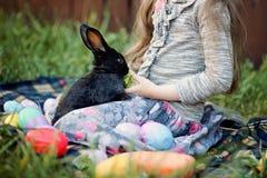 Jeu d'enfants avec le vrai lapin L'enfant riant à l'oeuf de pâques chassent avec le lapin blanc d'animal familier Petite fille d' Photos stock