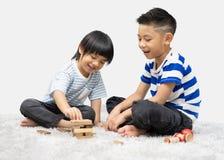 Jeu d'enfants avec un concepteur de jouet sur le plancher de la salle du ` s d'enfants Deux gosses jouant avec les blocs color?s photo stock