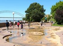 Jeu d'enfants dans l'eau au parc de rivière sur l'île de boue Image stock