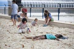 Jeu d'enfants dans le sable à la banque du sud de la Tamise dans l'heure d'été Photos stock