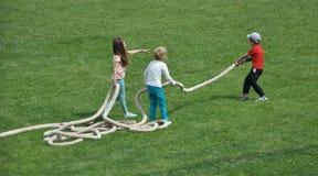 Jeu d'enfants en bas âge avec une corde photographie stock