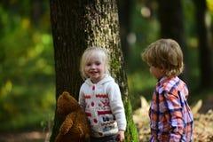 Jeu d'enfants heureux dans la famille heureuse, l'amitié, l'amour et la confiance de forêt d'automne Image stock