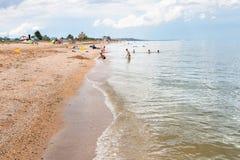 Jeu d'enfants sur le sable et la mer de plage d'Azov coquillière Photographie stock libre de droits