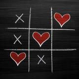 Jeu d'orteil de tac de tic avec des coeurs de craie, des riens de XO et le style de jour du ` s de Valentine de croix Photo libre de droits