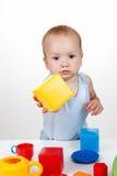 Jeu de bébé avec le cube en jouet dans le sourire bleu de robe Photos stock