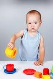 Jeu de bébé avec le jouet dans le sourire bleu de robe Image libre de droits