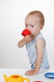 Jeu de bébé avec le jouet dans le sourire bleu de robe Photo libre de droits