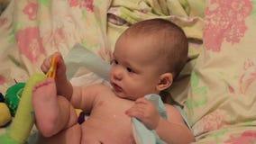 Jeu de bébé avec un jouet sur le lit banque de vidéos