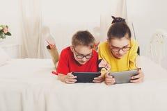 Jeu de deux enfants aux comprimés se trouvant sur le lit Image libre de droits