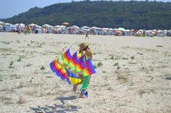 Jeu de fille avec le cerf-volant coloré de bateau de navigation Photographie stock