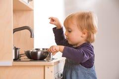Jeu de fille de fille de famille de bébé faisant cuire dans la cuisine de jouet Image libre de droits