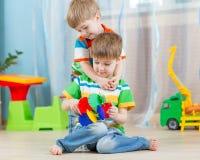 Jeu de frères d'enfants avec les jouets éducatifs à l'intérieur Photo libre de droits