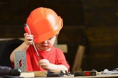 Jeu de garçon comme constructeur ou réparateur, travail avec des outils Enfant rêvant de la future carrière dans l'architecture o Photographie stock libre de droits