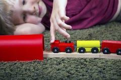 Jeu de garçon d'enfant avec le train en bois, chemin de fer de jouet de construction à la maison ou Photo stock