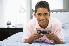 jeu de garçon de bâti se trouvant écoutant le vidéo d'adolescent Images stock