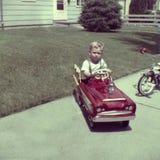 Jeu de garçon de rétro photo de vintage jeune dans la voiture de pédale Images stock
