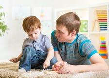 Jeu de garçon et de père d'enfant avec des jouets Images libres de droits